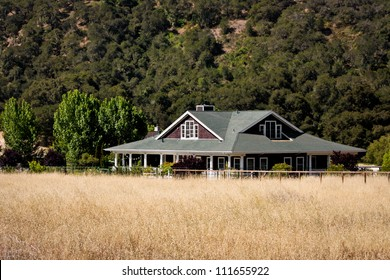 A ranch house situated on rural property with a hayfield in the foreground.