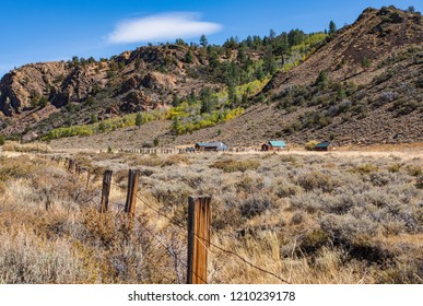 Ranch in the shadow of mountain with foliage, sagebrush and fence line