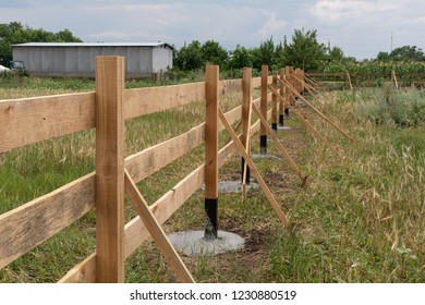 Ranch style fence. Rural wooden fence on green grass at farm ranch land in Shagany, Ukraina.