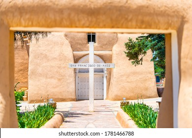 Ranchos de Taos St Francic Plaza and San Francisco de Asis church with cross and gate entrance on sunny day in New Mexico