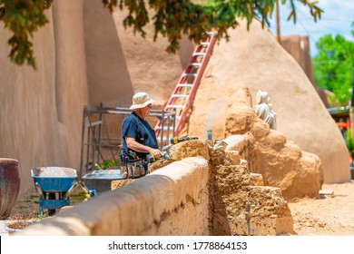 Ranchos de Taos, USA - June 19, 2019: St Francic Plaza and San Francisco de Asis church with man renovating during construction in New Mexico of North America