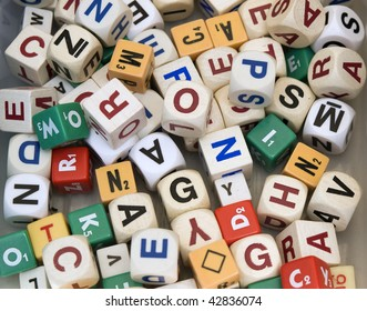 Random array of dice with alphabet letters, of the type typically used in games or to construct words for educational purposes.