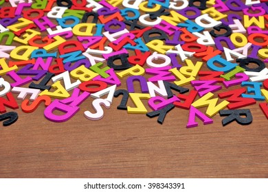 Random English Wooden Multicolored Letters On the Brown Wood Background, Close Up, Top View, Horizontal Image