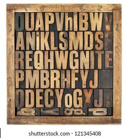 random letters of alphabet - vintage letterpress wood type blocks in rustic box isolated on white