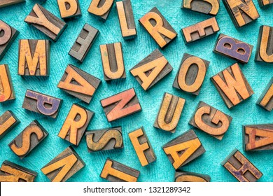 random letters overhead background - vintage letterpress wood type (inverted image)  against tuquoise bark paper