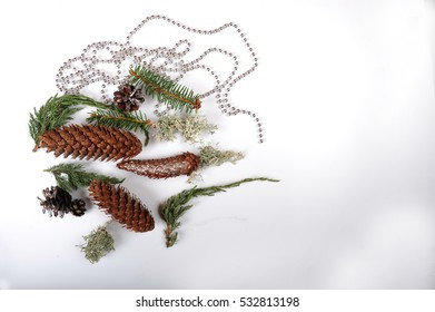 Random mix of pine cones, spruce cones, lichen, juniper and spruce twigs. Silver girland of tiny silver balls.  Copy space in the right side of image.