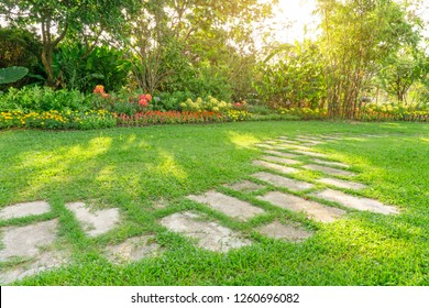 Random pattern of grey concrete stepping stone on green grass lawn, flowering plant, shrub and trees on backyard under morning sunshine with good care landscaping in a garden of the public park