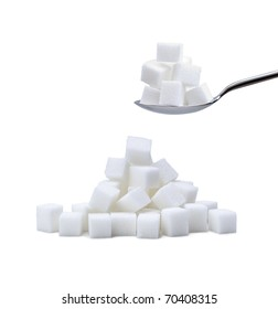 random pile of refined white sugar cubes with a second pile on a steel spoon on white background