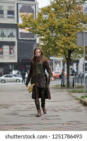 Random portrait of a girl who goes on the sidewalk. She is dressed in a boho style: brown coat, yellow bag, green sweater, shorts and torn stockings