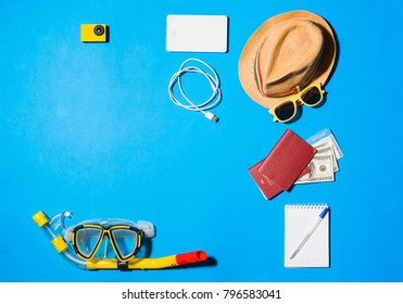 Random travel objects on blue background. Overhead view.