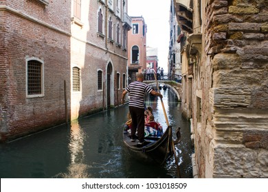 A random water canal in Venice, Italy. Gondolier guy carrying the random tourist with his gondola. He wears special t-short that all gondoliers wear.It is traditional costume for them. Date:30.05.2017