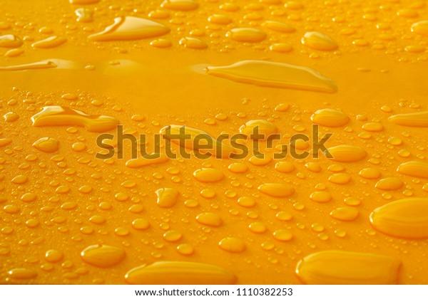 random water drops on flat yellow surface after rain