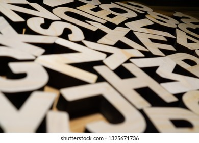 Random wooden block letters lying on wooden background.