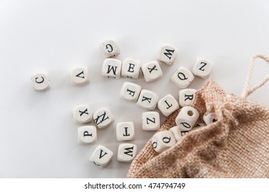 Randomly letter on dice falls out from burlap sack