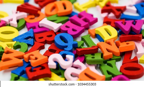 Randomly scattered colorful wooden letters on a white background.