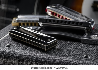 Randomly scattered harmonicas on the guitar amp. The set of diatonic blues harps for playing country and western.
