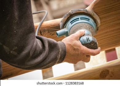 Random-orbit disc sander held in grip of man's hand; refinishing piece of custom wooden furniture.