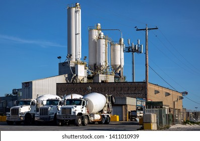 A range of cement mixer trucks  in a parking lot of a cement factory