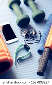 range of fitness, physiotherapy, electronics, and yoga equipment on a blue mat