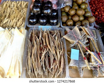 A range of foods for sale in a Vietnamese market. These include dried seahorse, dried lizards, and colourful vegetables and roots.