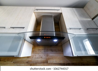 Range Hood in the kitchen interior. Stainless Steel Cooker Hood with light on. Kitchen Wall Mount Range Hood with Tempered Glass and Touch Control. Cooking Hoods. Chimney Hood. Kitchen Appliances