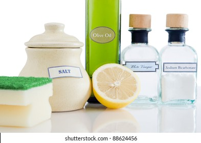 A range of natural, non-toxic cleaning products in containers on a shiny reflective surface with a white background.