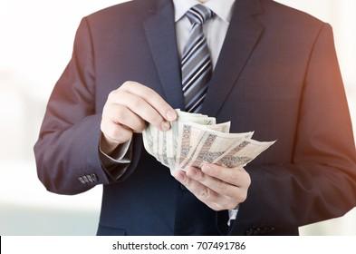 Range of Polish banknotes in hand. businessman giving money loan polish zloty pln hand concept