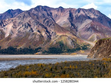 A range of rugged, purple mountains towers over a braided river and tundra in fall colors during late autumn in Denali National Park, Alaska, under a cloudy blue sky