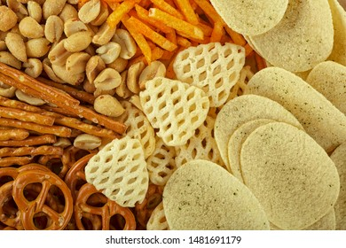 Range of salty snacks, as background. Pretzels, potato chips, crackers and salty straw.