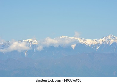 A range of snow-covered mountains are seen against a blue sky. Soft clouds are below their peaks. Forest covers the slopes in the foreground.