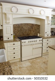 Range style cooker in a modern kitchen interior with granite worktop and cream units