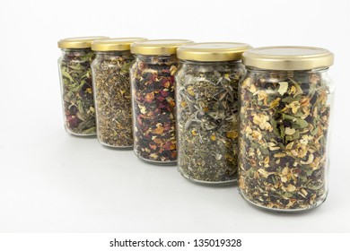 A range of transparent glass jars of different herbs.