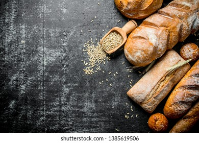 The range of types of fresh bread with grain. On dark rustic background