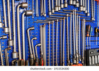 A range of used mechanic tools, from combination wrenches to screwdrivers and socket wrench. All hanging on blue panels. Perfect shot for arts and crafts.