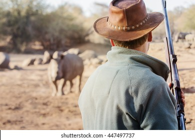 Ranger with firearm stands face to face with rhino and watches the behavior of the rhino.