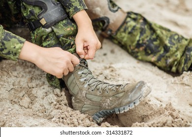 rangers boots and hands tying bootlaces in desert