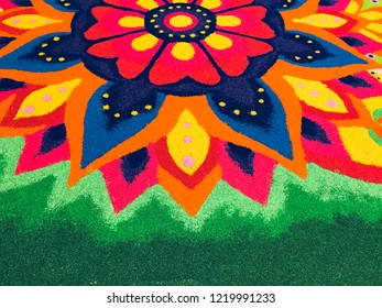 Rangoli is an art form, originating in the Indian subcontinent, in which patterns are created on the floor or the ground using materials such as colored rice, dry flour, colored sand or flower petals.