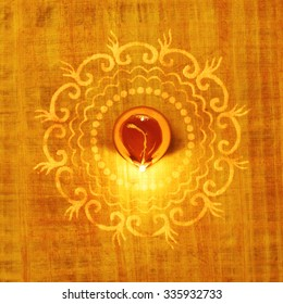 Rangoli design around traditional terra-cotta lamp. Indian religious background.