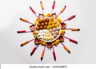 Rangoli or design made using Diya/oil lamp, flowers and sweets likeGulab Jamun, Rasgulla, kaju katli, morichoor / Bundi Laddu, Gujiya or Karanji for diwali celebration