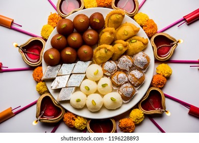 Rangoli or design made using Diya/oil lamp, flowers and sweets likeGulab Jamun, Rasgulla, kaju katli, morichoor / Bundi Laddu, Gujiya or Karanji for diwali celebration