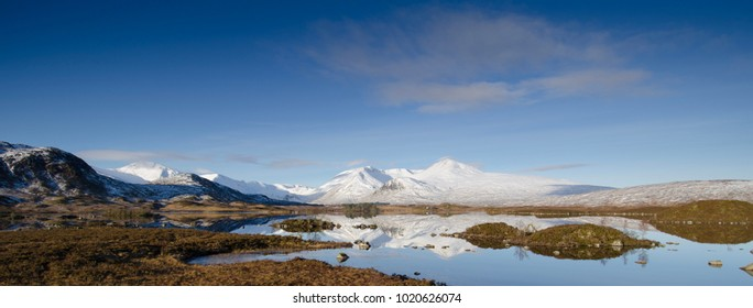 Rannoch Moor, wilderness, Scottish Highlands. Stunning snow topped mountains, mirrored in the watery foreground of boggy, moorland which supports a variety of wildlife. Rich, rusty coloured marshland.