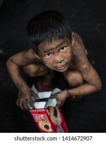 Ranong, Thailand-On August 6, 2016. Portrait of poor Asian Boy opening dessert box at coal industry. Dirt on kid's hand, face, body.