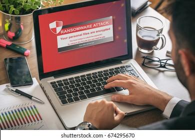 Ransomware alert message on a laptop screen - man at work
