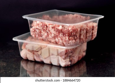 ransparent resealable vacuum plastic trays filled with fresh raw minced meat and pieces of raw chicken. Food delivery concept. Black background. Selective focus