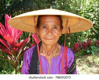 RANTEPAO, SULAWESI, INDONESIA - SEPT 13, 2010: Old Toraja woman wears a flat Asian conical straw hat (caping) and poses for the camera in the countryside of Central Sulawesi, on Sept 13, 2010.