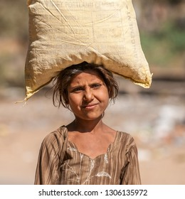 RANTHAMBORE, INDIA - FEBRUARY 4, 2011: Rajasthani girl carries a heavy load on her head. Rajasthani people are known as some of the most colorful people in India.