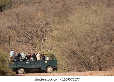 RANTHAMBORE, INDIA-MAY 05: Tourist on canter trying to locate a tiger down the river at Ranthambore National Park, Sawai Madhopur, India on May 05, 2018