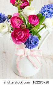 ranunculus and hyacinth flowers in a pitcher on wooden surface