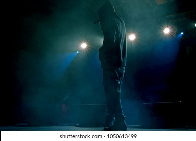 Rap artist on stage in the rays of soffits light. Concert backlight and illumination during music concert. Singer in hoodie with microphone at stage