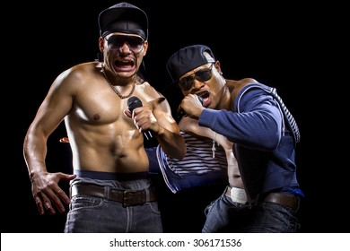 Rap concert with two muscular shirtless men with microphones.  The musicians are hip hop artists.